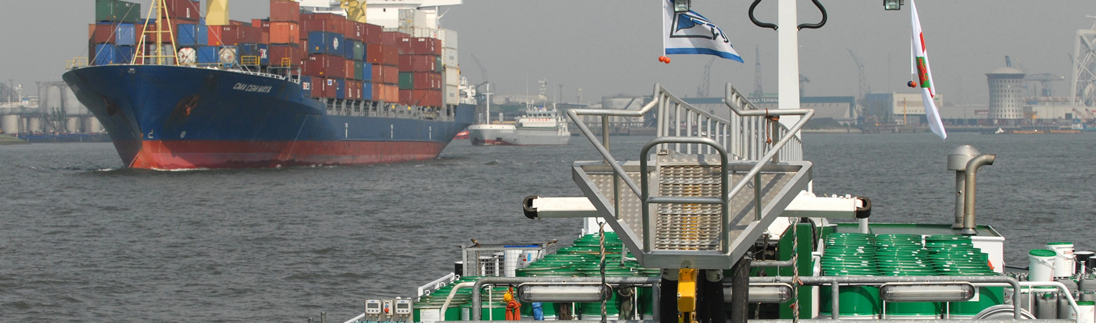 M.t.'s product barge Vanora carrying barrels of lubricant passes a container cargo ship in Rotterdam Harbour, Netherlands.