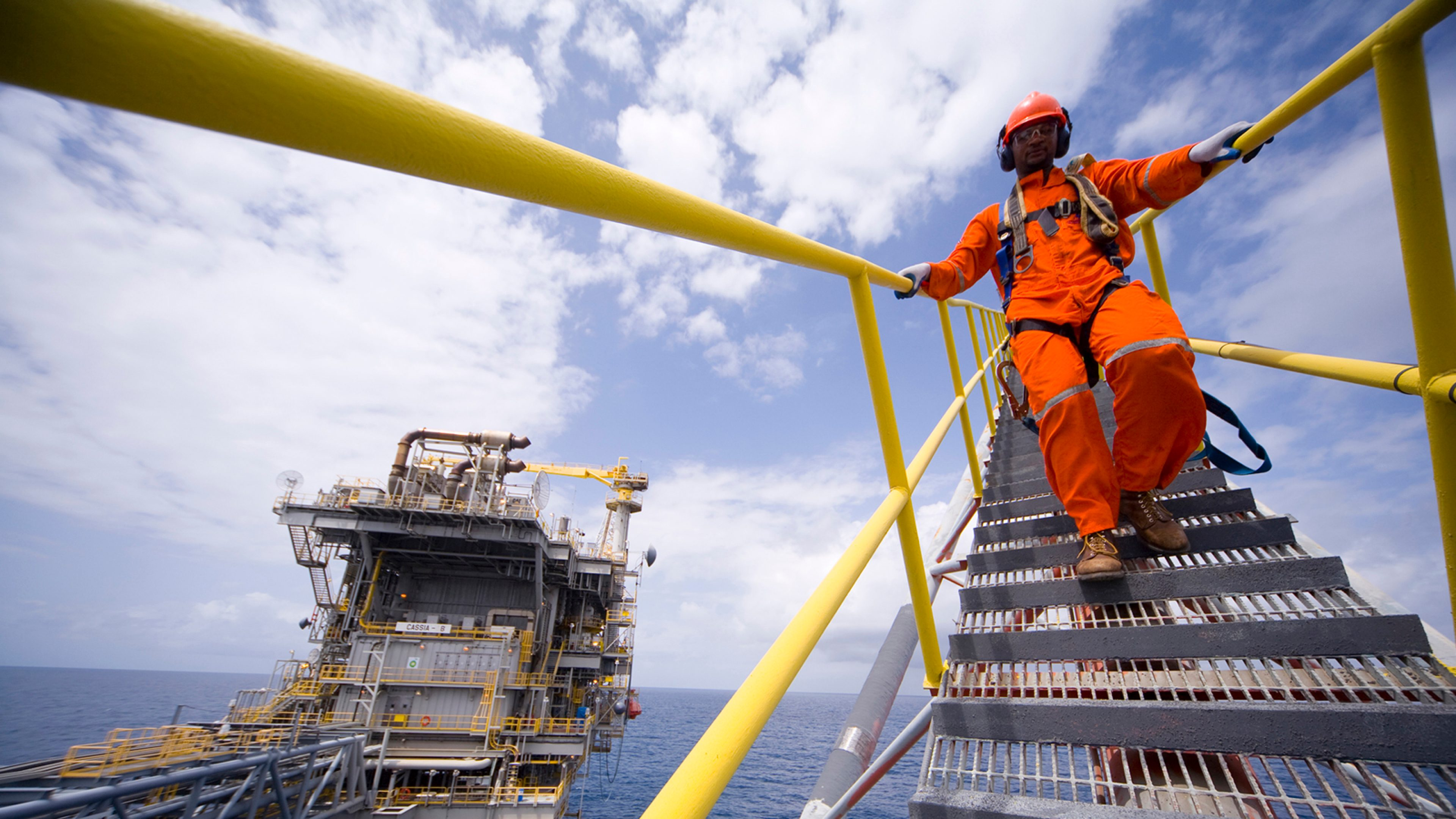 An operator walking down a stairwell while holding the handrail on board the Cassia A and Cassia B platforms, offshore Trinidad.