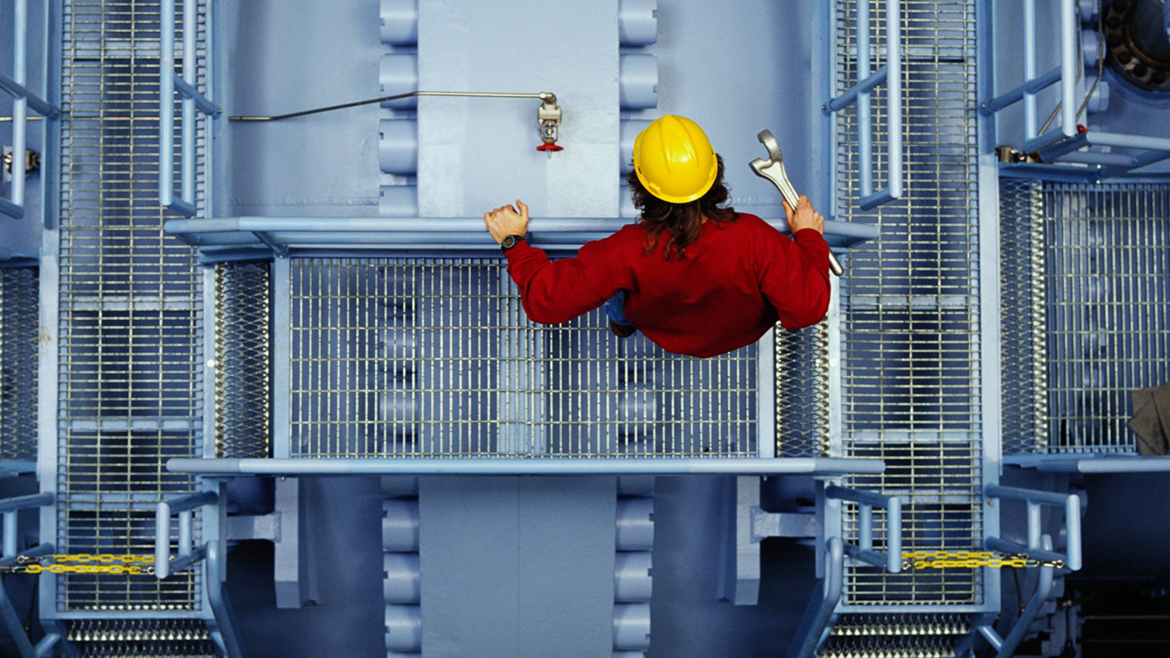 Worker inspecting valve at power station. overhead view --- Image by © Ocean/Corbis