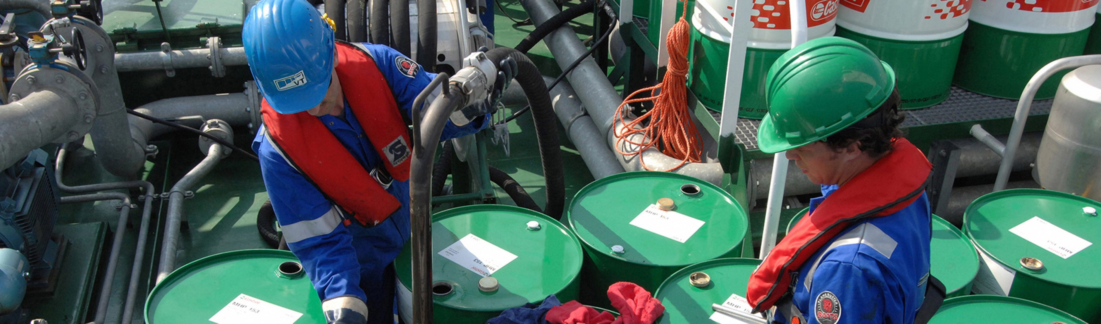 Operators pump marine lubricants from drums on m.t.'s product barge Vanora's deck to the customer ship in Rotterdam, Netherlands.