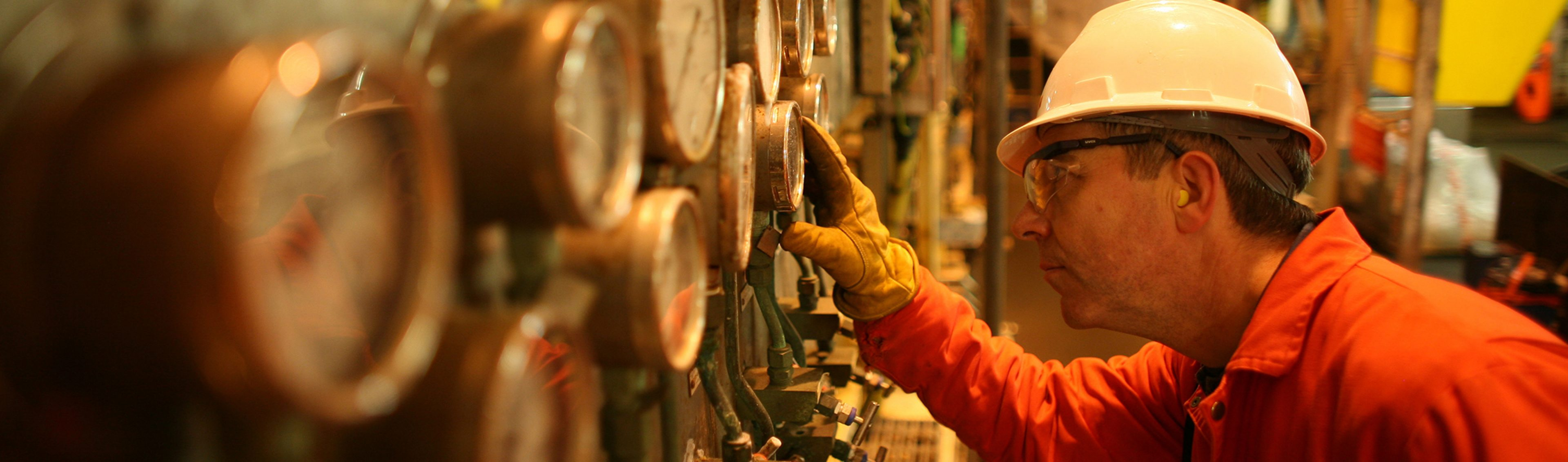 An Operations Technician takes a reading (monitoring) of the LP compressor gauge on board the Bruce platforms located north-east of Aberdeen, in the Northern North Sea, UK.